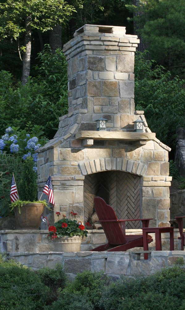 Tan brick outdoor fireplace by patio furniture, shrubbery, and yard decor