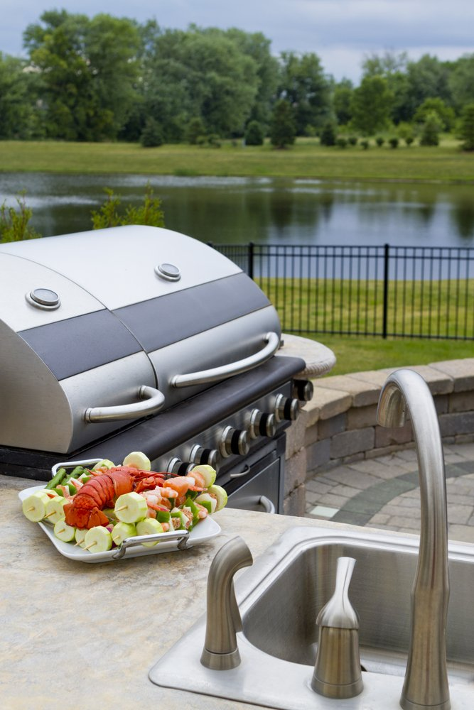 Outdoor grill and sink in backyard with an outdoor kitchen